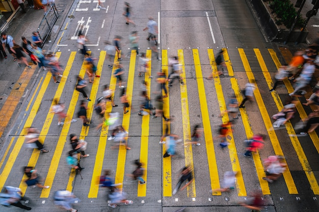 Top view scene of motion blurred crowd unrecognizable pedestrians crossing over the hong kong street around mong kok station, yellow color zebra is the sign of hong kong transportation and crosswalk