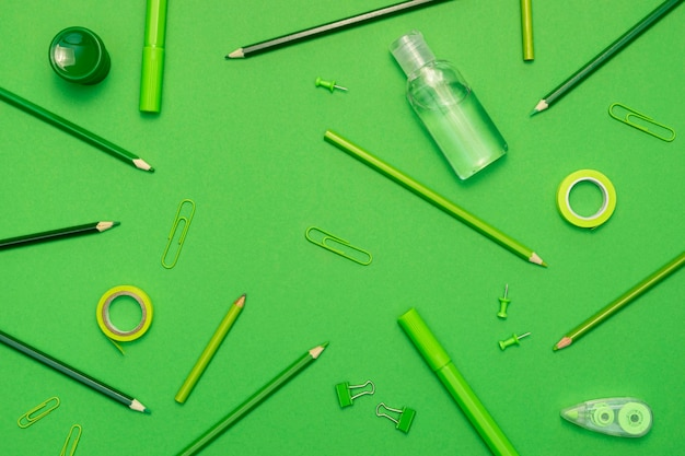 Top view school items on green background