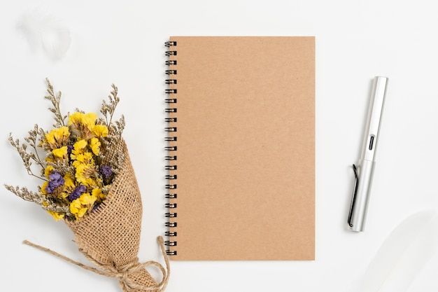 Top view of school spiral notebook with pen and static flowers on white background