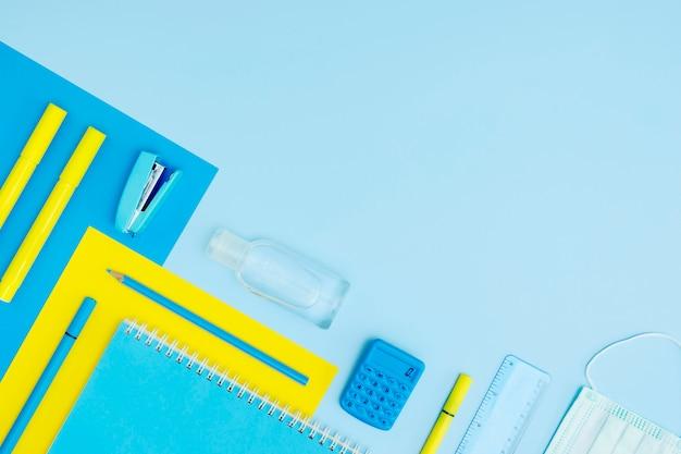 Вид сверху школьные принадлежности на синем фоне