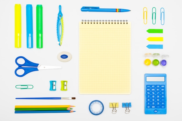 Top view school supplies on a student desk on white background