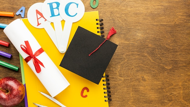 Top view of school supplies with academic cap and copy space