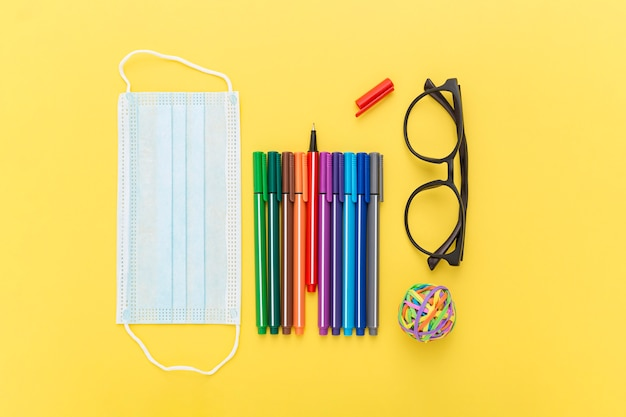 Top view of school supplies with face mask and glasses