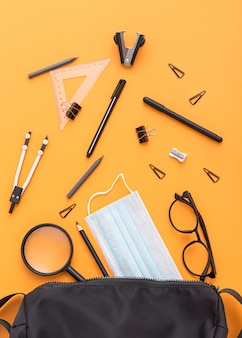 Top view of school supplies with face mask and magnifying glass