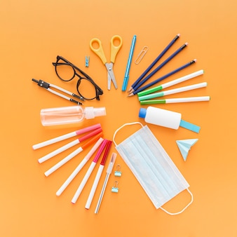 Top view of school supplies with face mask and pencils