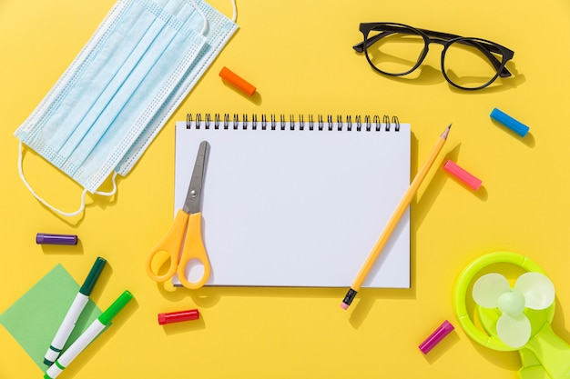 Top view of school supplies with glasses and notebook