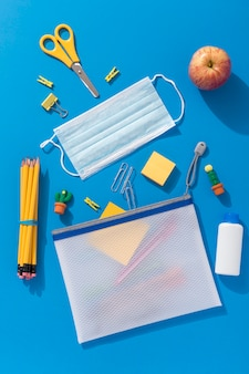Top view of school supplies with medical mask and apple