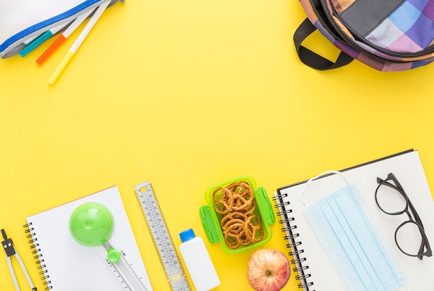 Top view of school supplies with notebook and glasses