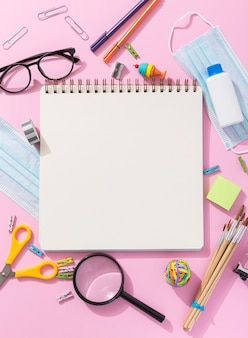 Top view of school supplies with notebook and magnifying glass