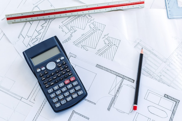 Top view of a scientific calculator on construction blueprints and tools for sketches