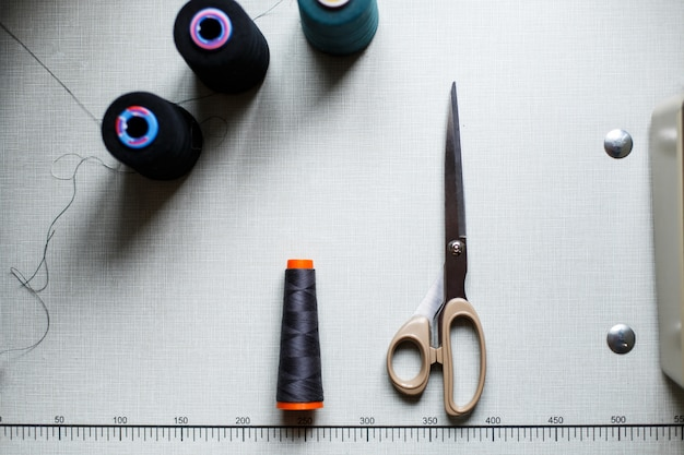 Top view of scissors and skeins of thread on a white table with markings