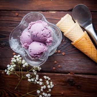 Вид сверху шариков черничного мороженого с вафельными рожками и гипсофилой и ложкой для мороженого в чашке для мороженого
