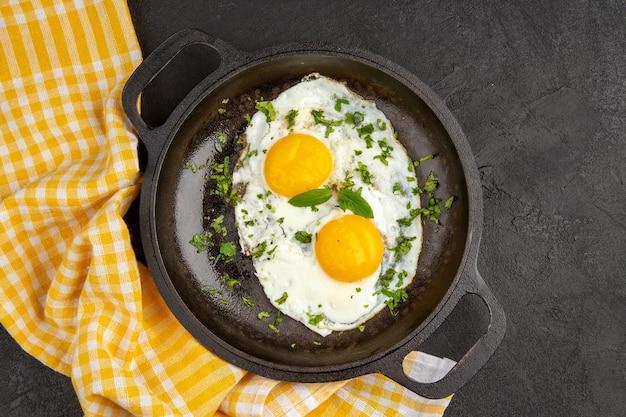 Вид сверху яичница с зеленью внутри сковороды на темном фоне завтрак хлеб еда еда цвет обед чай утренний омлет