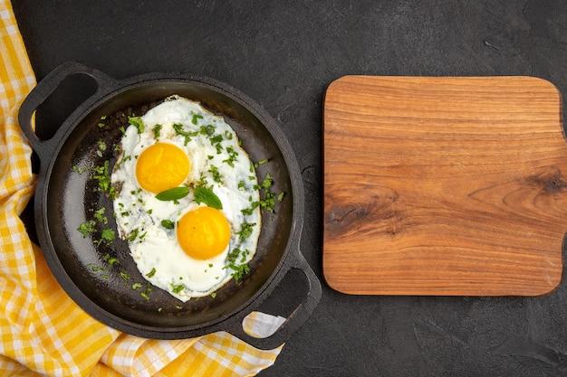 Вид сверху яичница с зеленью внутри сковороды на темном фоне завтрак хлеб еда еда цвет чай утренний омлет