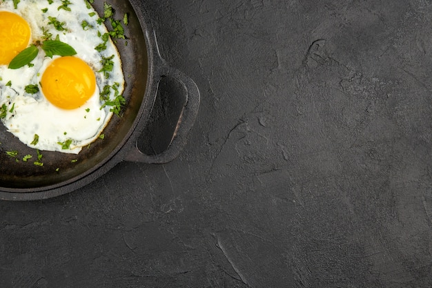 Вид сверху яичница с зеленью внутри сковороды на темном фоне завтрак еда еда цвет обед омлет хлеб чай утро бесплатное место