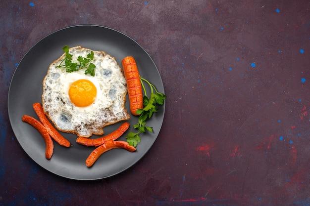 Vista dall'alto di uova strapazzate con verdure e salsicce all'interno della piastra sulla superficie scura