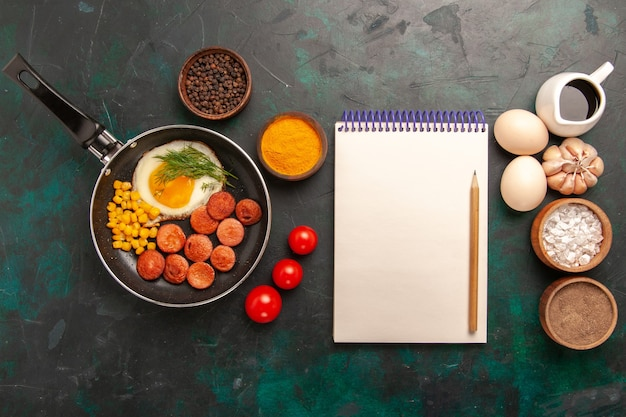 濃い緑色の机の上にソーセージとさまざまな調味料を添えたスクランブルエッグの上面図