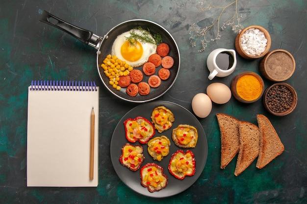 暗い背景にソーセージパンとさまざまな調味料とスクランブルエッグの上面図