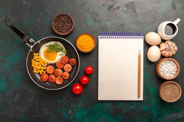 Vista dall'alto uova strapazzate con salsicce e condimenti diversi sulla scrivania verde scuro