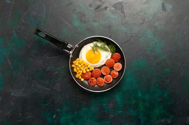 Top view scrambled eggs with sausages and greens on dark-green background