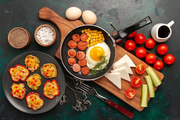 Top view scrambled eggs with sliced sausages fresh tomatoes and raw eggs on dark background