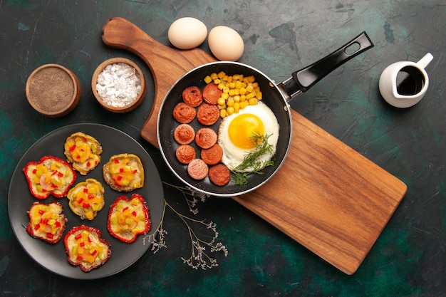 Vista dall'alto uova strapazzate con salsicce a fette e uova crude su sfondo scuro