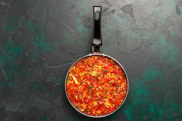 濃い緑色の背景の鍋の中にトマトと緑のスクランブルエッグの上面図