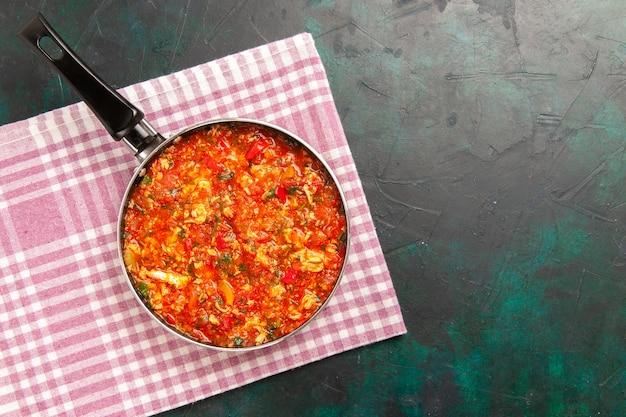 진한 녹색 배경에 팬 내부 토마토와 채소와 상위 뷰 스크램블 에그