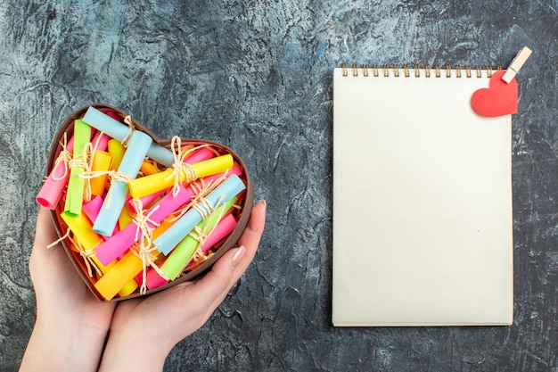 Свиток вид сверху цветные бумаги с пожеланиями в коробке в форме сердца в женской руке ноутбука с наклейкой в виде красного сердца на темном фоне