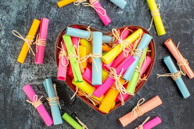 Свиток вид сверху цветные бумаги с пожеланиями в коробке в форме сердца на сером фоне