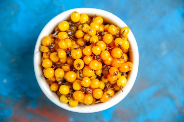 Top view of sea buckthorn in bowl on blue surface