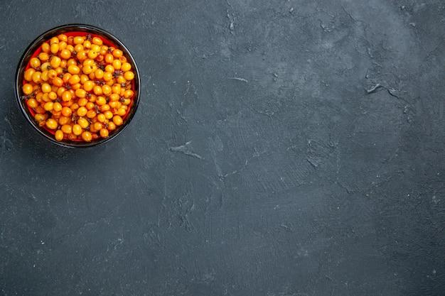 Olivello spinoso vista dall'alto nella ciotola sul tavolo scuro con lo spazio della copia