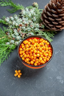 Top view sea buckthorn in bowl pine branch pinecone on dark red table