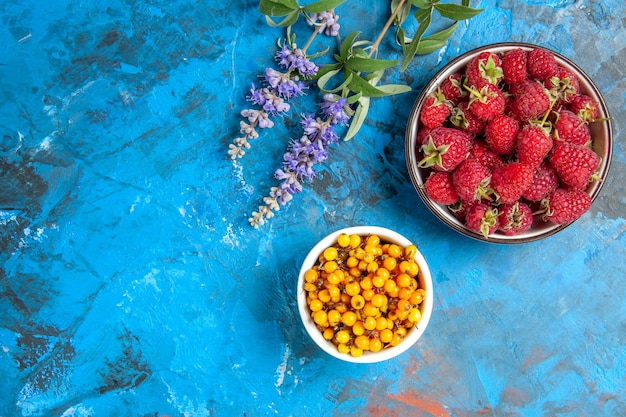 Top view of sea buckthorn in bowl raspberry bowl on blue surface