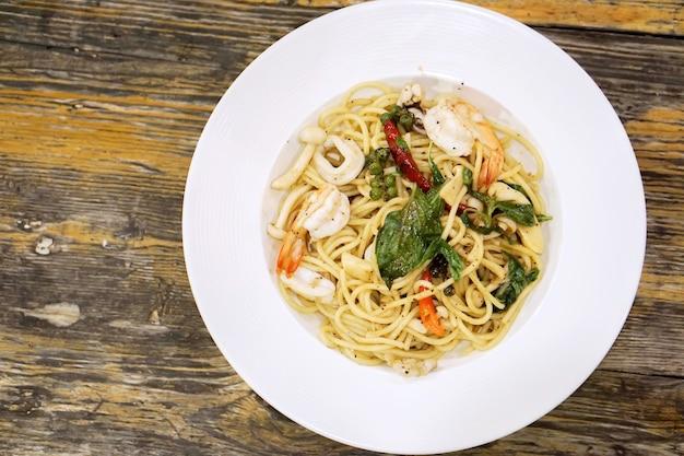 Спагетти из морепродуктов вида сверху зажаренные пряными спагетти в белой керамической тарелке на деревянном столе в ресторане.