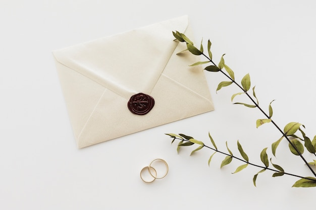 Top view sealed wedding invitation with engagement rings
