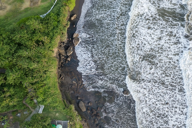 Top view seascape with waves breaking against the rocks