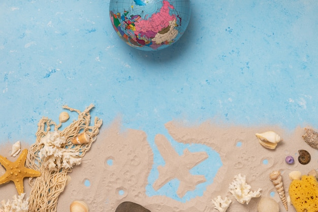 Top view of seashells, world globe and starfish on a beach