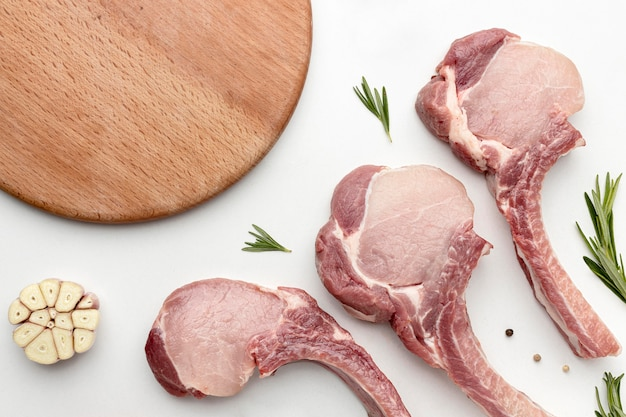 Вид сверху приправленное мясо для приготовления пищи с деревянной доской