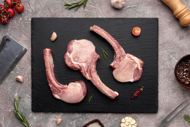 Вид сверху приправленное мясо на деревянной доске