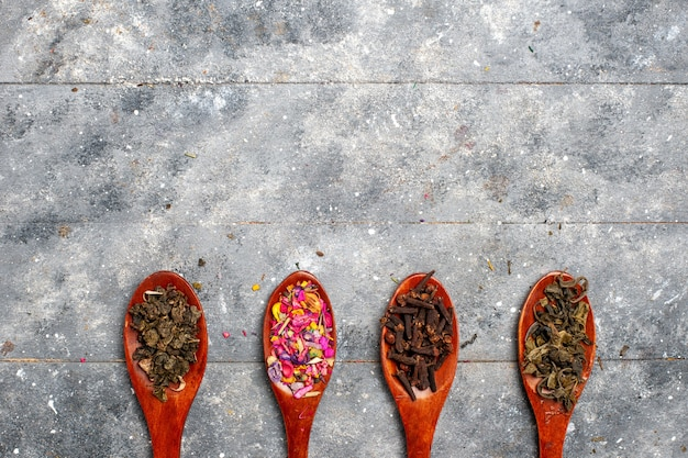 Vista dall'alto composizione di condimento di diversi colori all'interno di cucchiai sul colore della pianta secca del tè grigio scrivania
