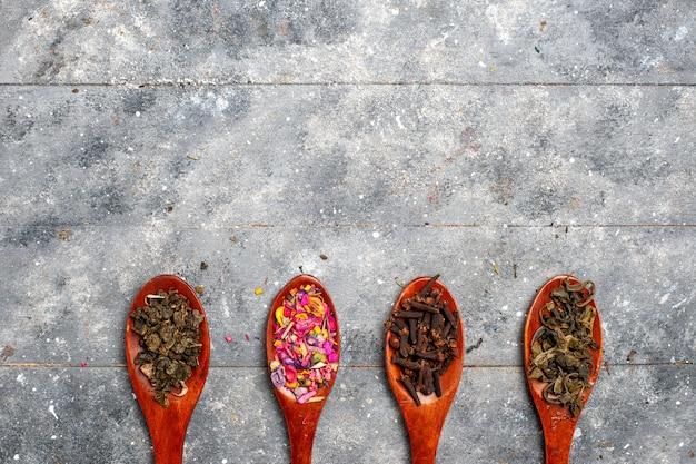 灰色の机のお茶の乾燥した植物の色のスプーンの内側の異なる色の調味料組成物の上面図