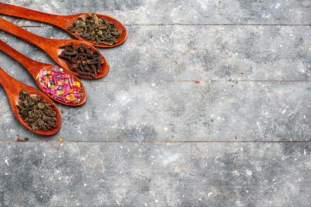 Композиция приправы, вид сверху, разноцветная внутри ложек на сером деревенском столе, цвет сухого растения