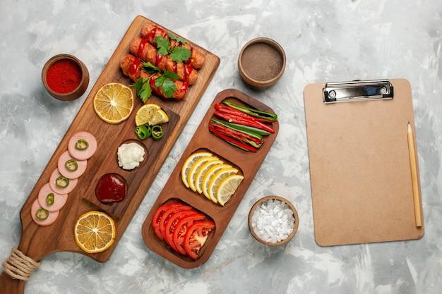 Вид сверху приправы и овощи с лимоном и сосисками на белом столе