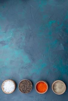 Vista dall'alto condimenti e sale all'interno di ciotole sullo sfondo blu scuro pepe sale condimento foto a colori