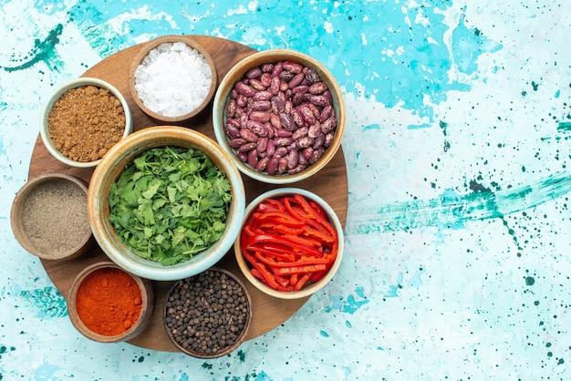 Vista dall'alto condimenti con verdure e fagioli sullo sfondo azzurro condimento verde pepe foto a colori