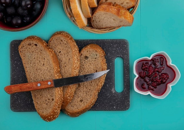 Top view of seeded brown cob slices with knife on cutting board and raspberry jam with sloe berries and baguette slices on blue background