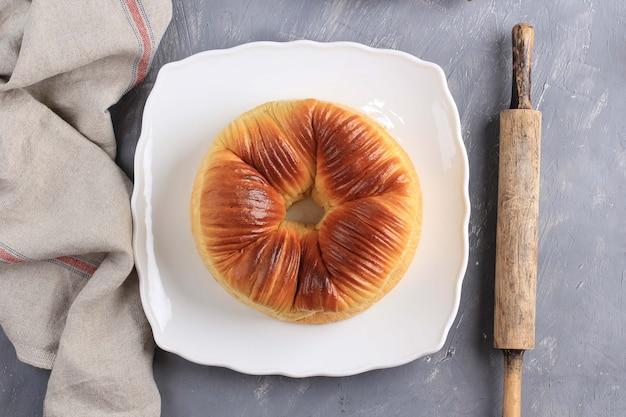 トップビュー厳選されたフォーカスウールロールパン、自家製ウイルスの日本のブリオッシュ北海道羊毛のような美しい食感の食パンミルクパン。白いプレート、コピースペースのあるセメントの背景で提供