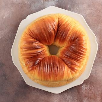 トップビュー厳選されたフォーカスウールロールパン、ウールのような美しい質感の自家製ウイルス日本ブリオッシュミルクパン。灰色のプレート、コピースペース付きのピンクの背景で提供
