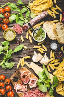 Top view of selection of italian traditional food, appetizers and snacks as salami, prosciutto, cheese, pesto, ciabatta, olive oil, pasta on rustic wooden background